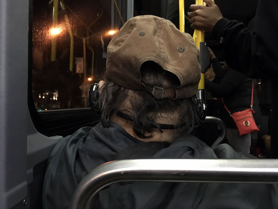 a man on a bus, pictured from the back