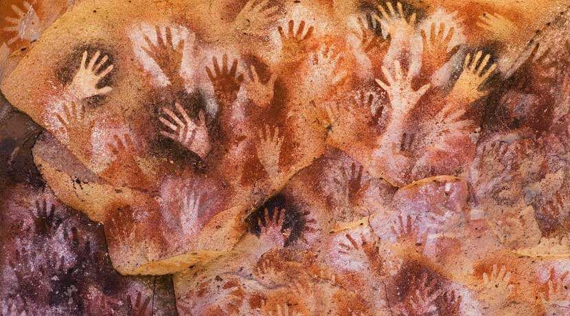 prehistoric hand prints on cave wall
